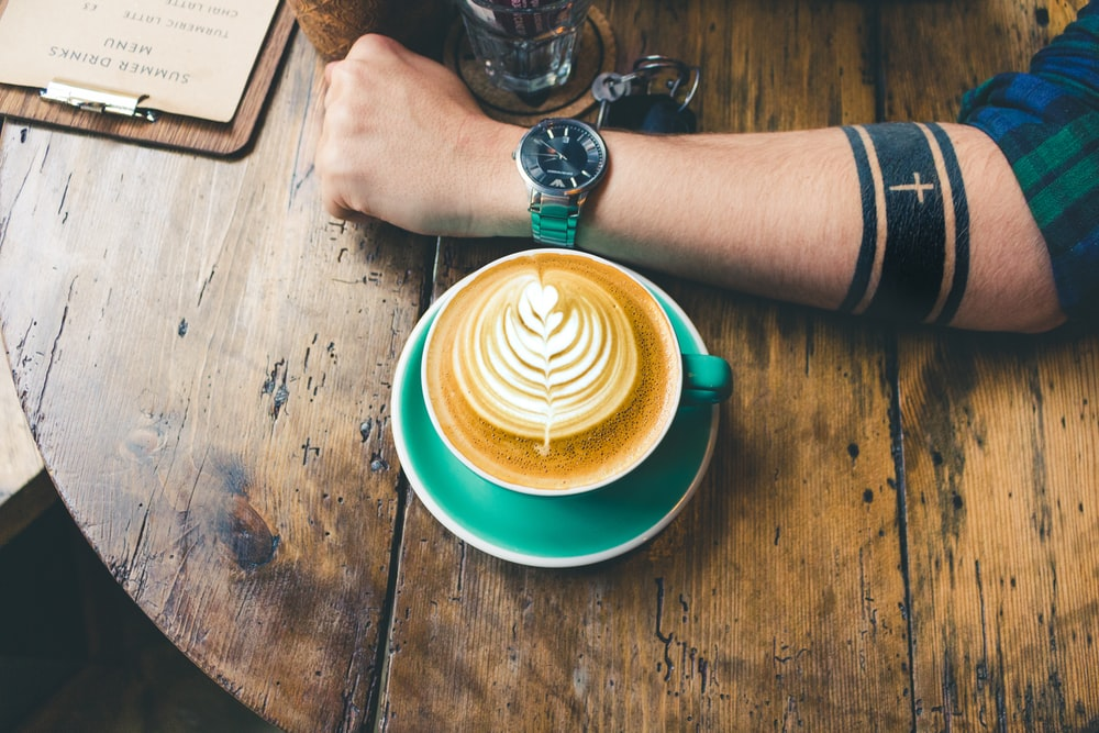 cappuccino next to man's arm whose wearing watch