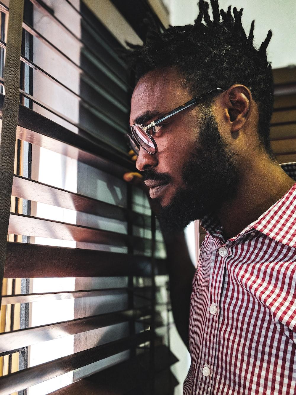 man looking through the window blind inside room