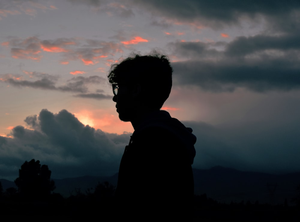 silhouette photography of man standing near trees