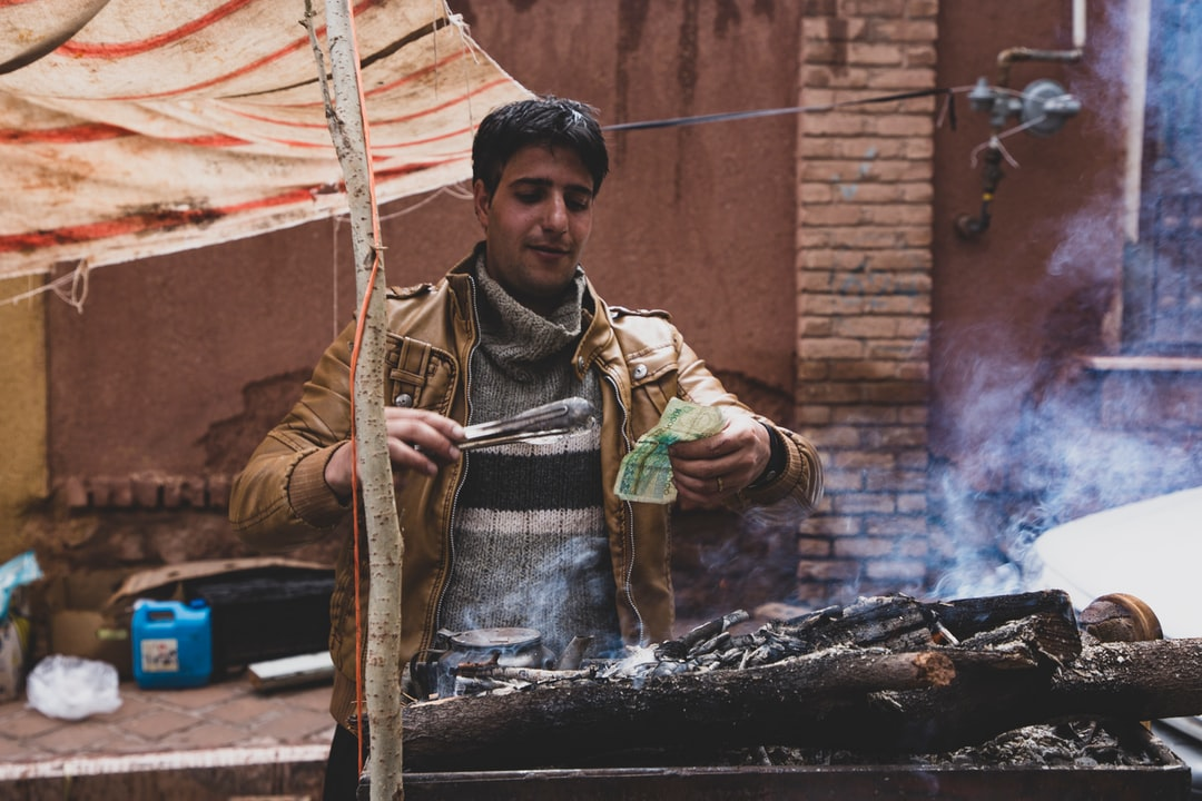 The vendors are selling baked corn. The note was wet from the sudden afternoon rain, so he tried to bake it dry.