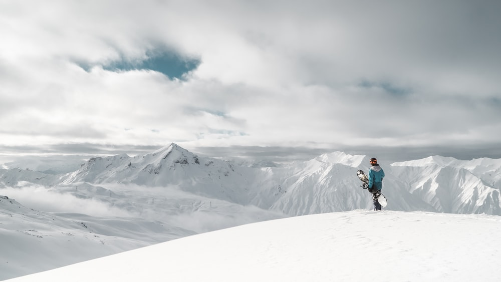 person standing on white snow cliff