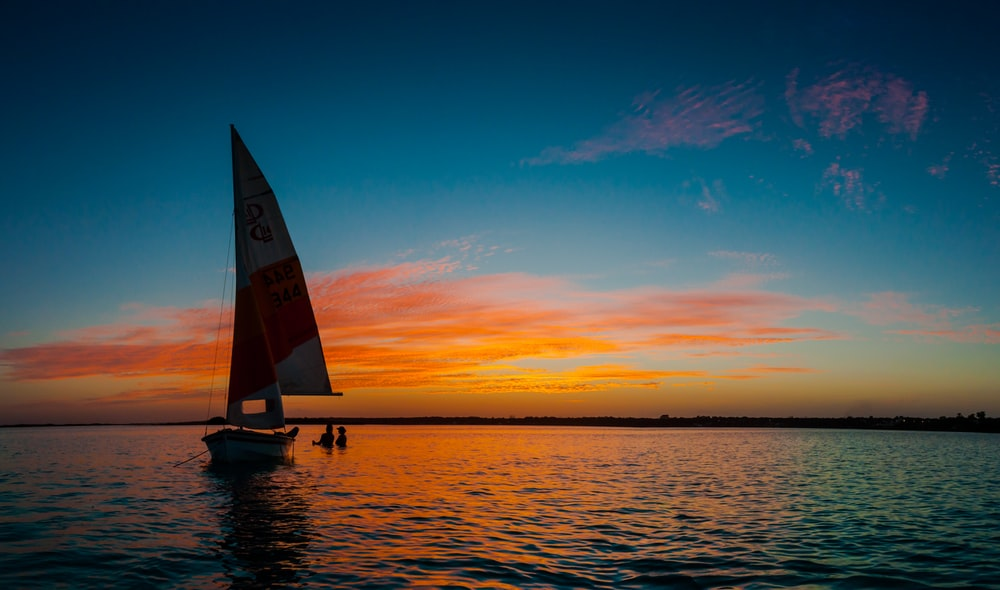 silhouette photo of white sail boat