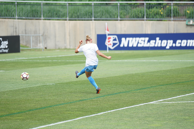 woman kicked soccer ball on soccer field