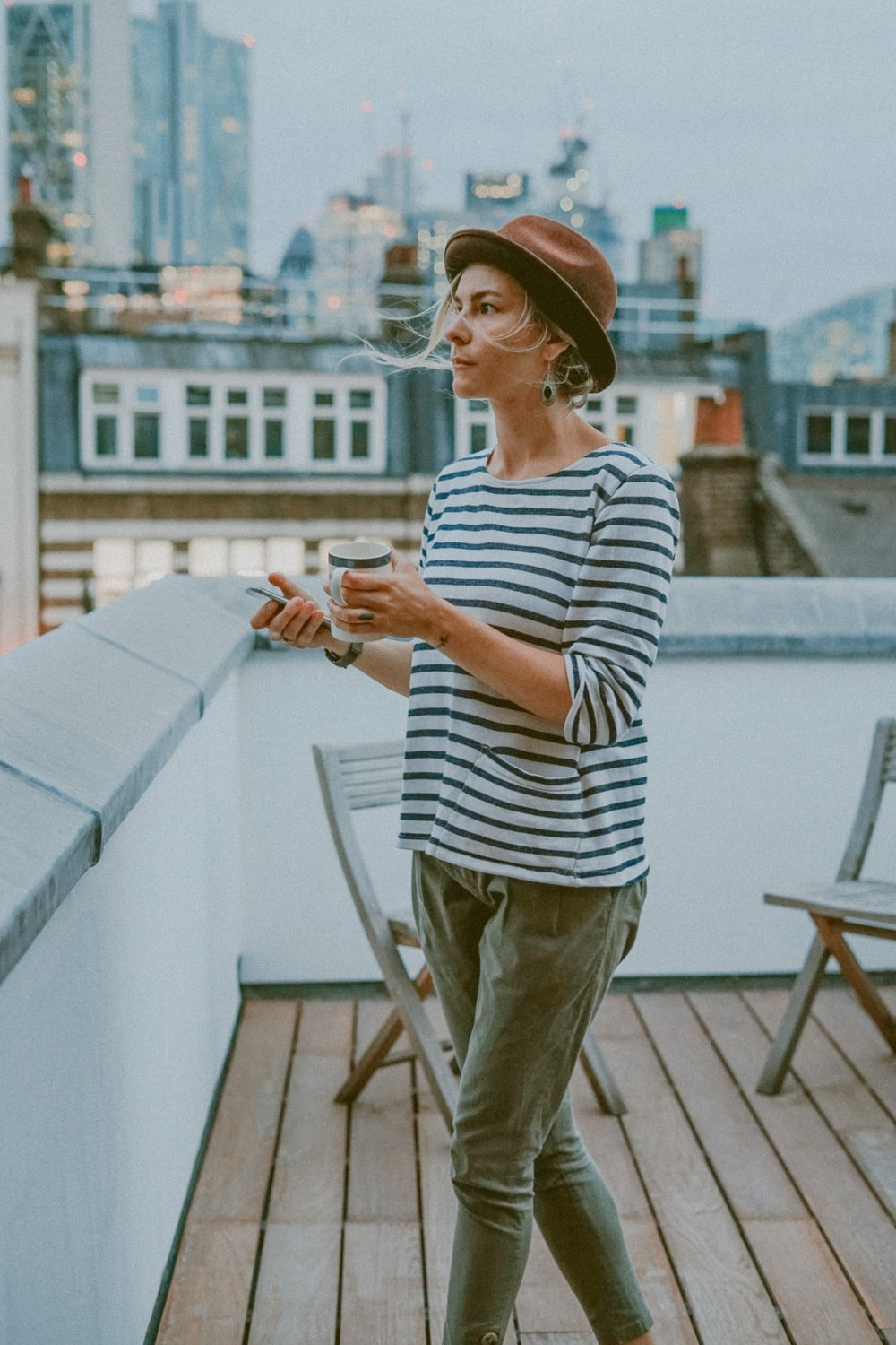 woman in white and black striped shirt holding mug