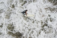 person in body of water holding surfboard