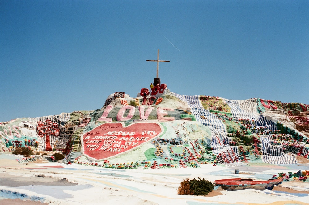assorted-color land formation with cross on top