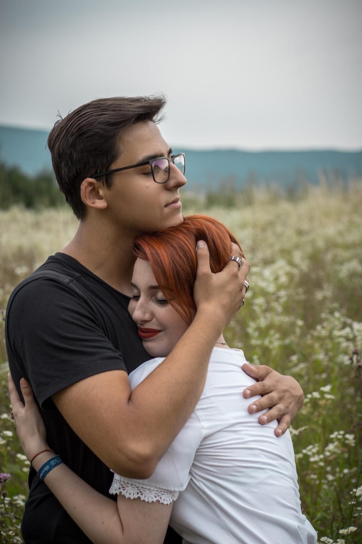 man hugging woman on flower field