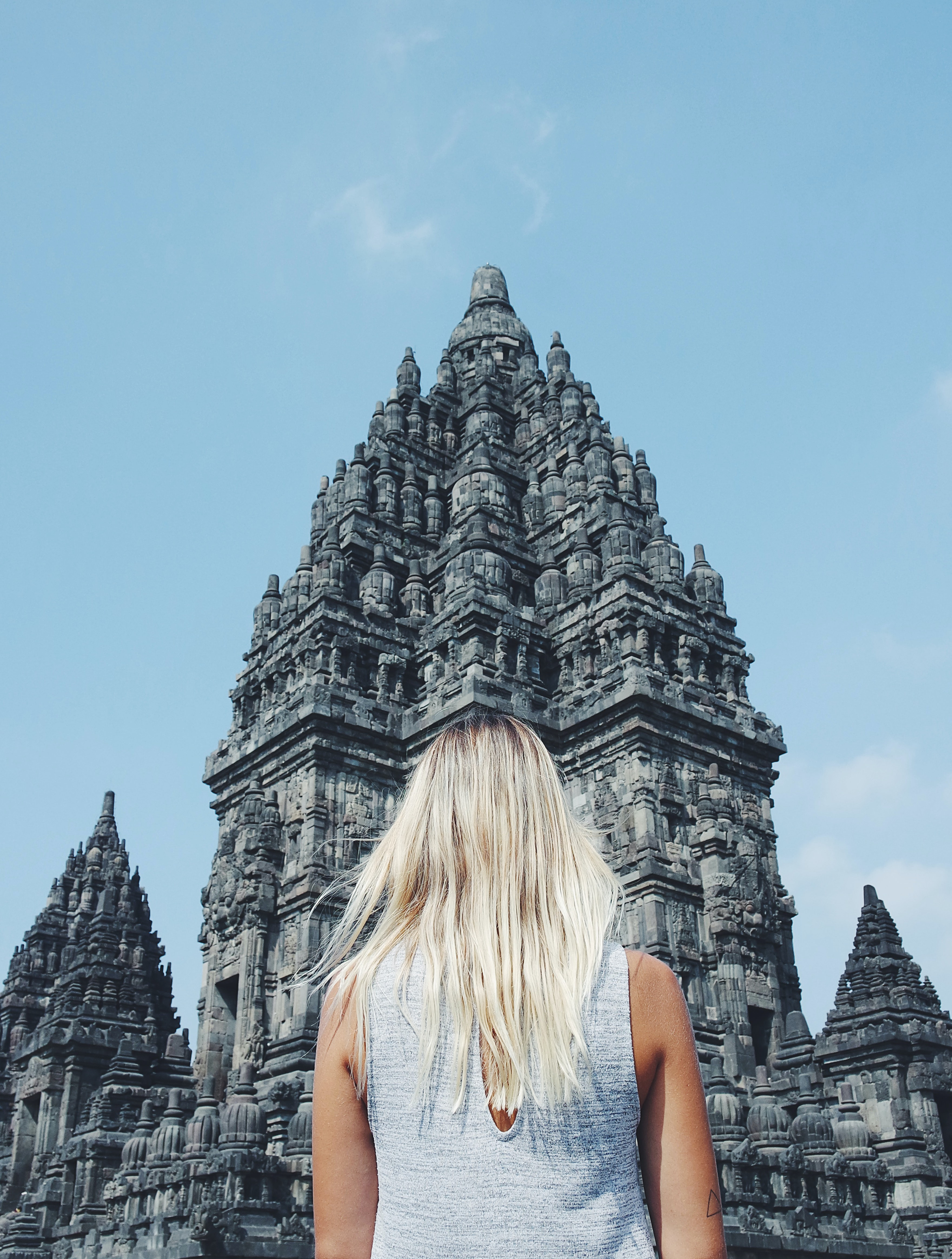 blonde haired woman standing in front of concrete temple