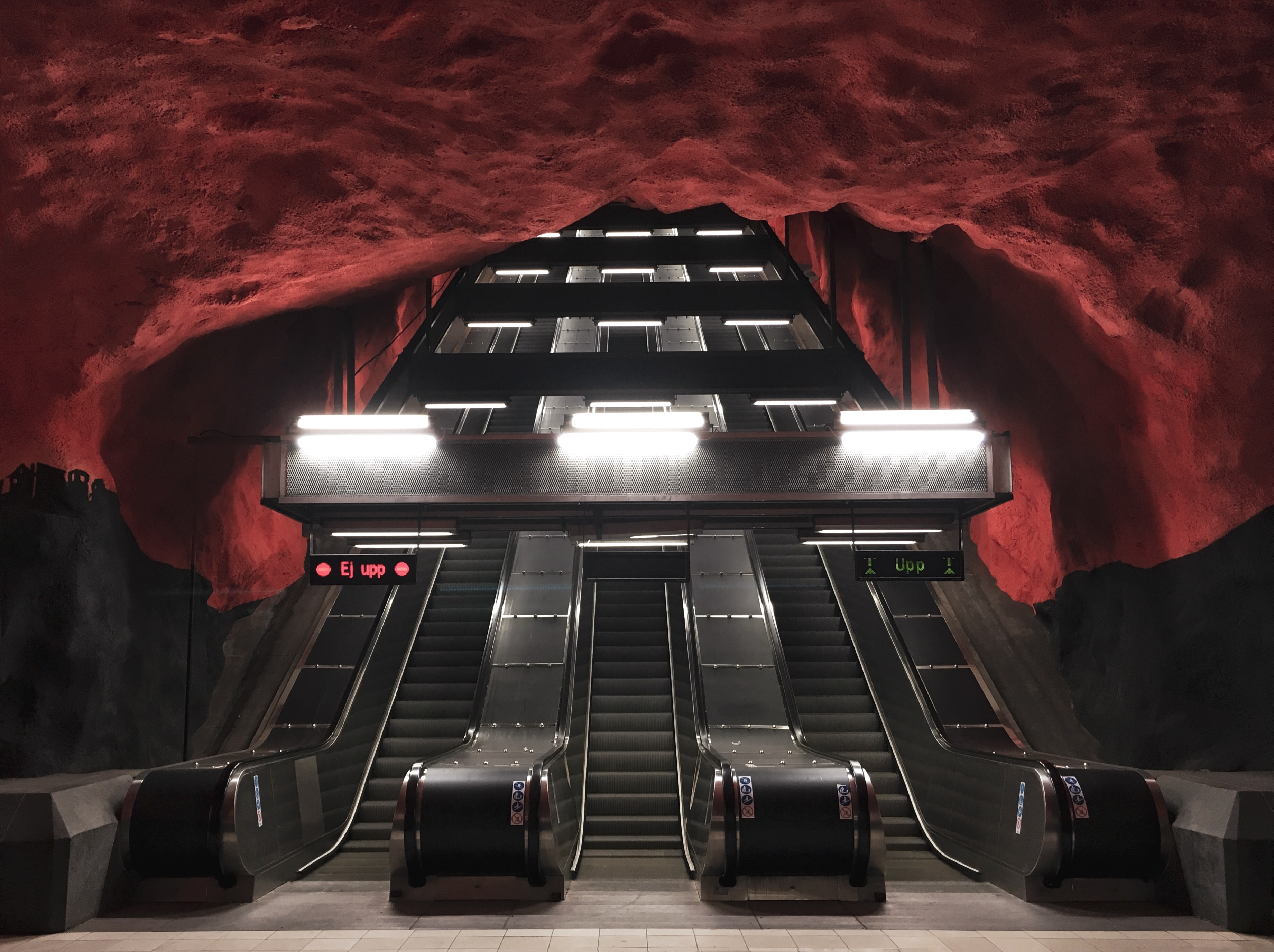 three black escalators inside red and black room