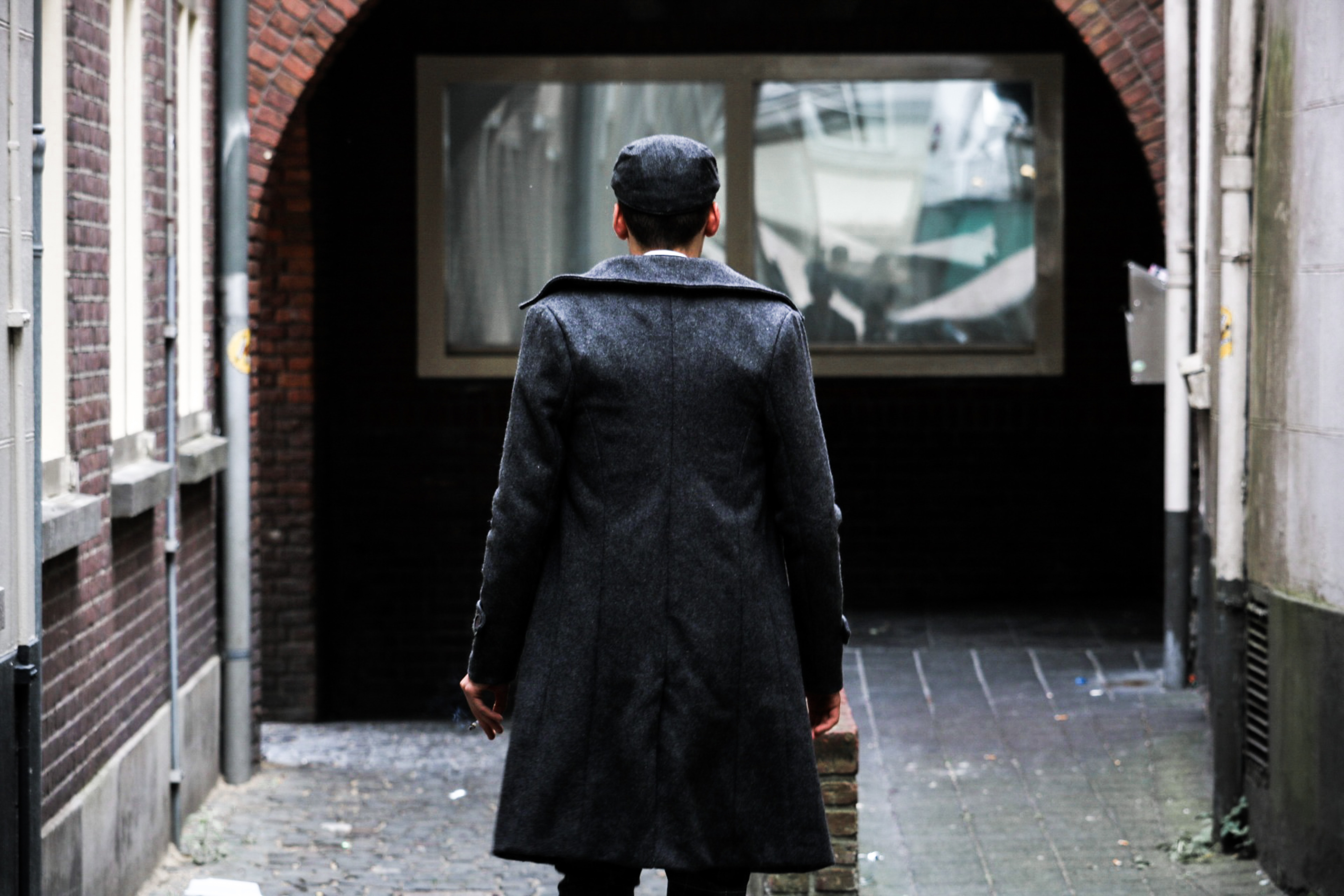 person in black long coat standing near clear glass window