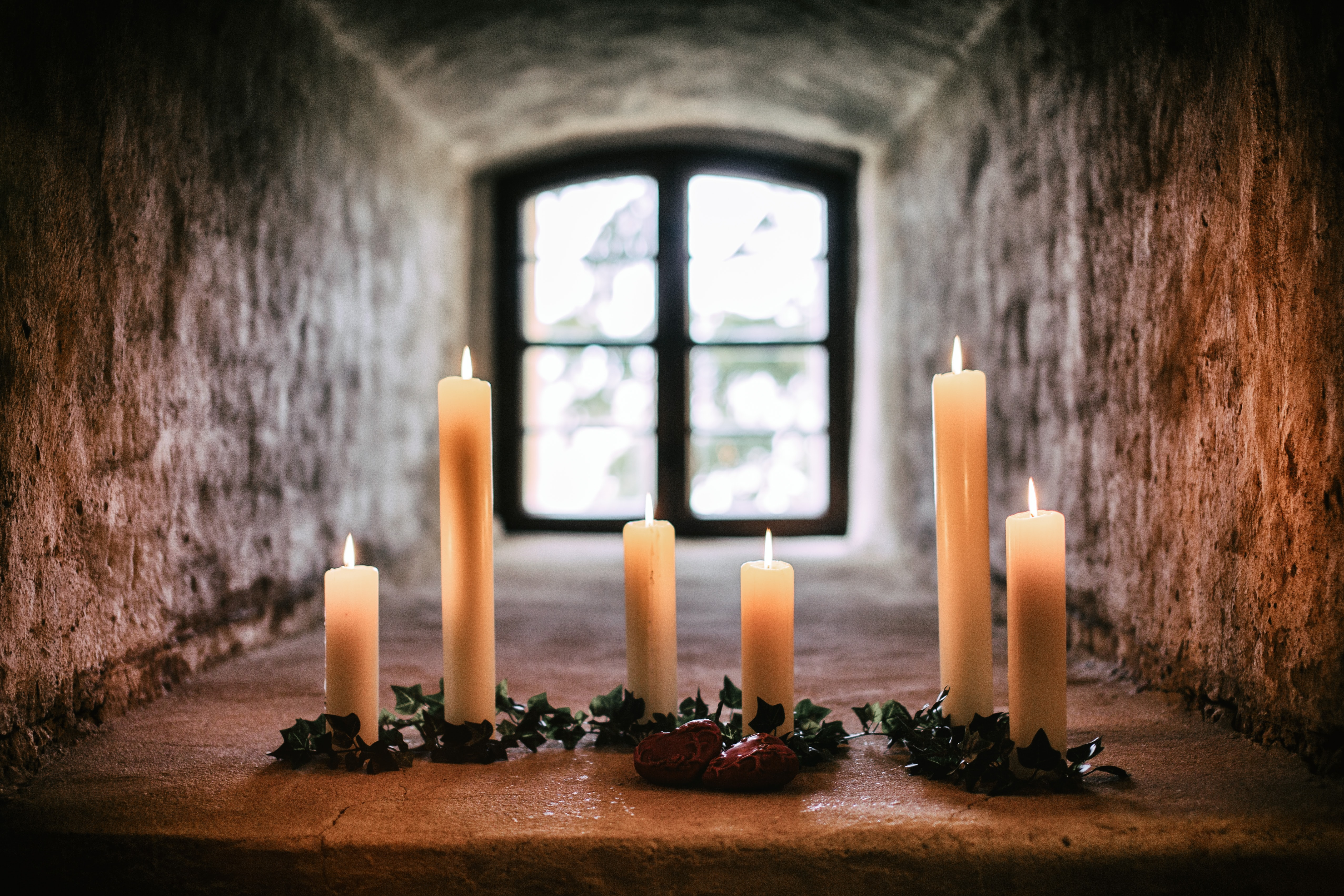 six white taper candles standing on gray concrete pavement in room