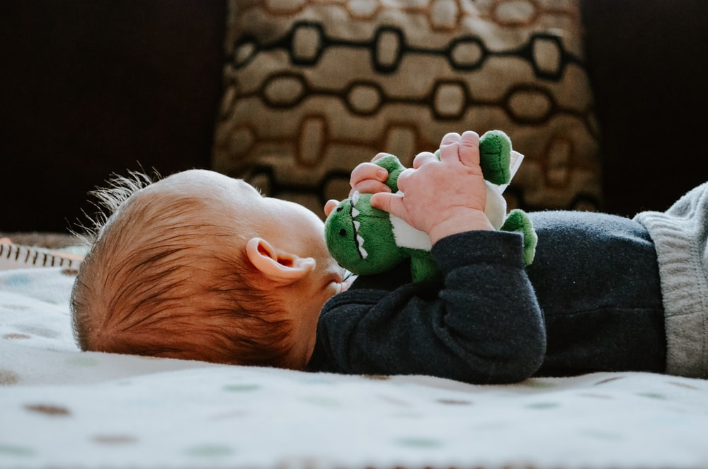 baby lying on white bed