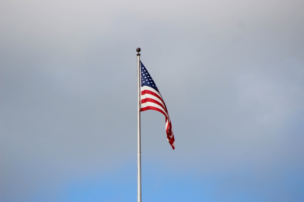 waving US flag under grey cloudy sky