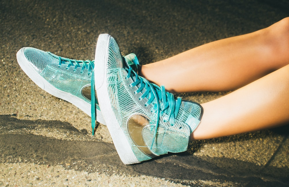 person showing teal Nike shoes