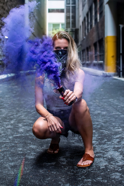 woman bending on concrete pavement holding blue smoke