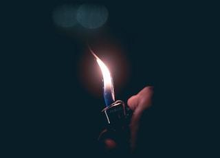 person holding lit lighter at dark room