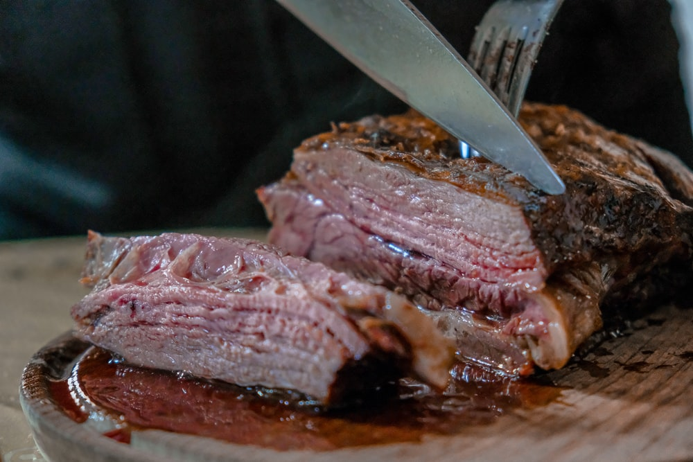 person slicing juicy medium rare meat on top of brown wooden cutting board