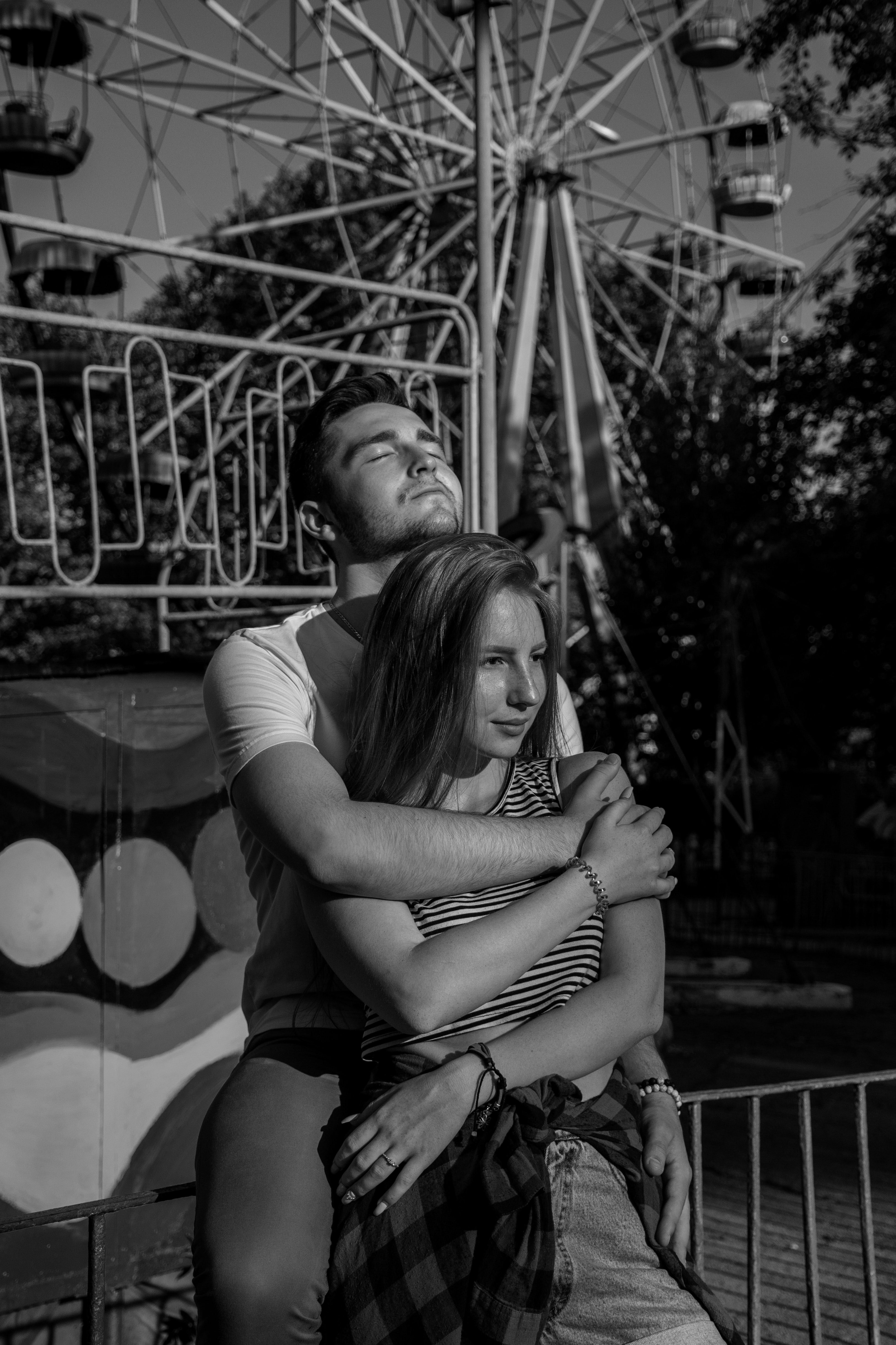 grayscale photo of man hugging woman near Ferri's wheel