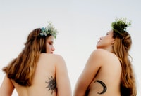 two naked women with sun and crescent moon tattoos