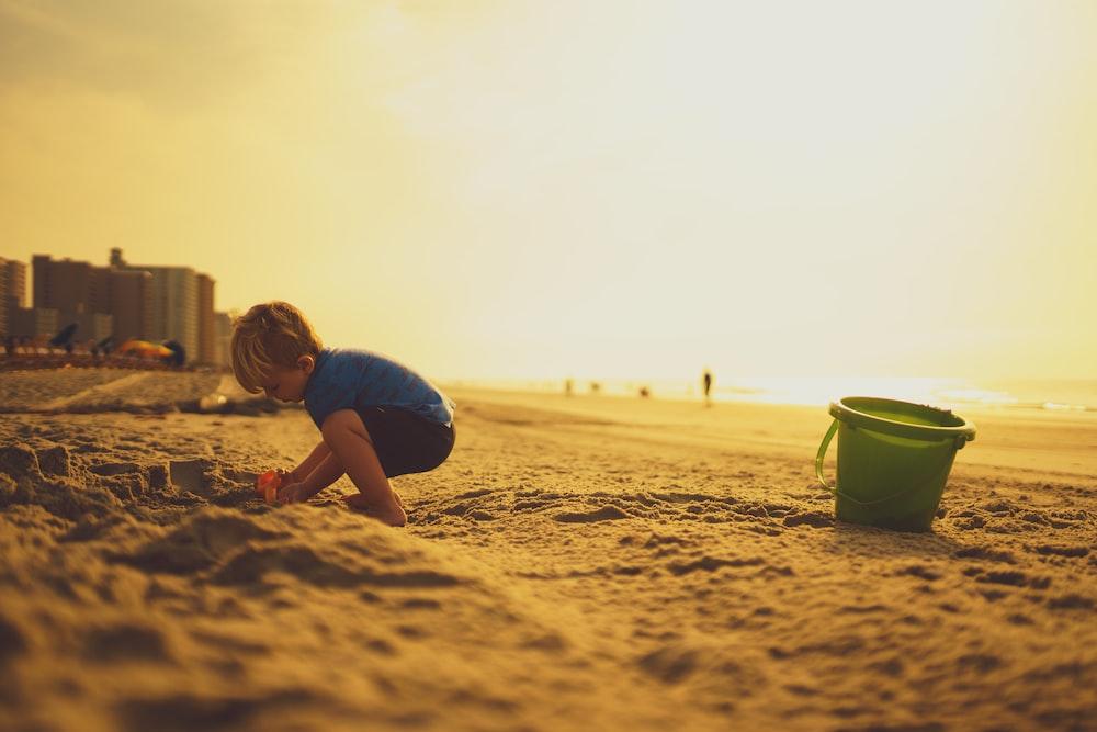 child playing on sand near pail