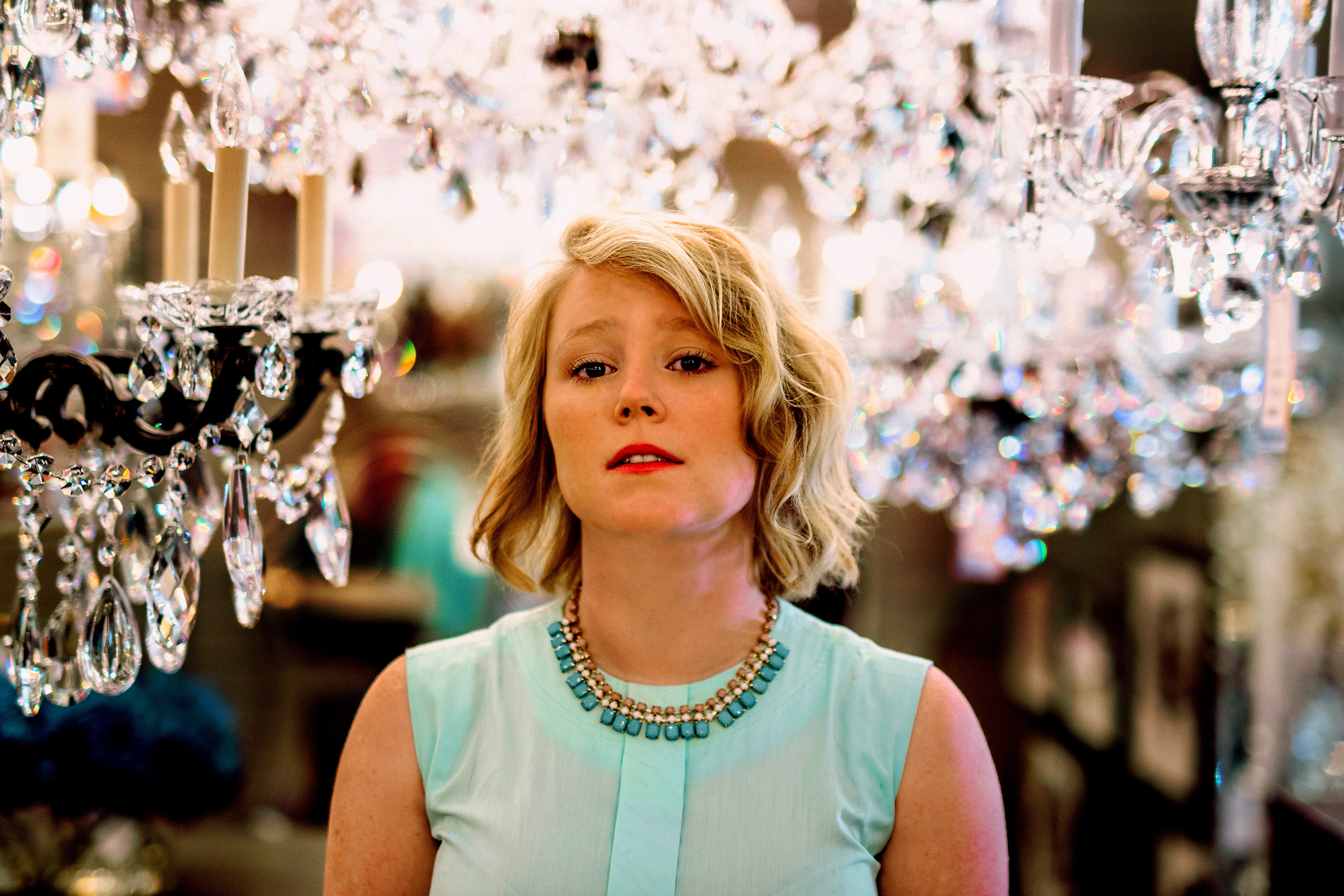 woman in teal sleeveless top standing surrounded by glass chandelier