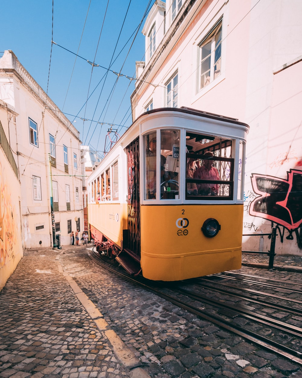 yellow and white tram climbing up hill