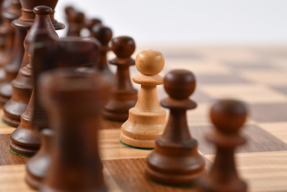 brown wooden chess pieces on chessboard