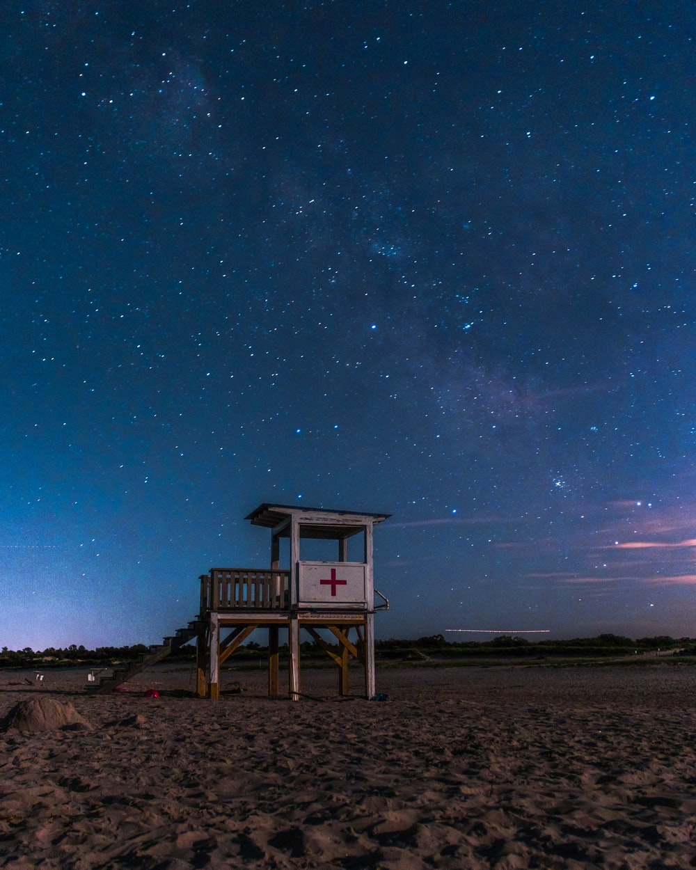 white lifeguard shed on beach under starry sky