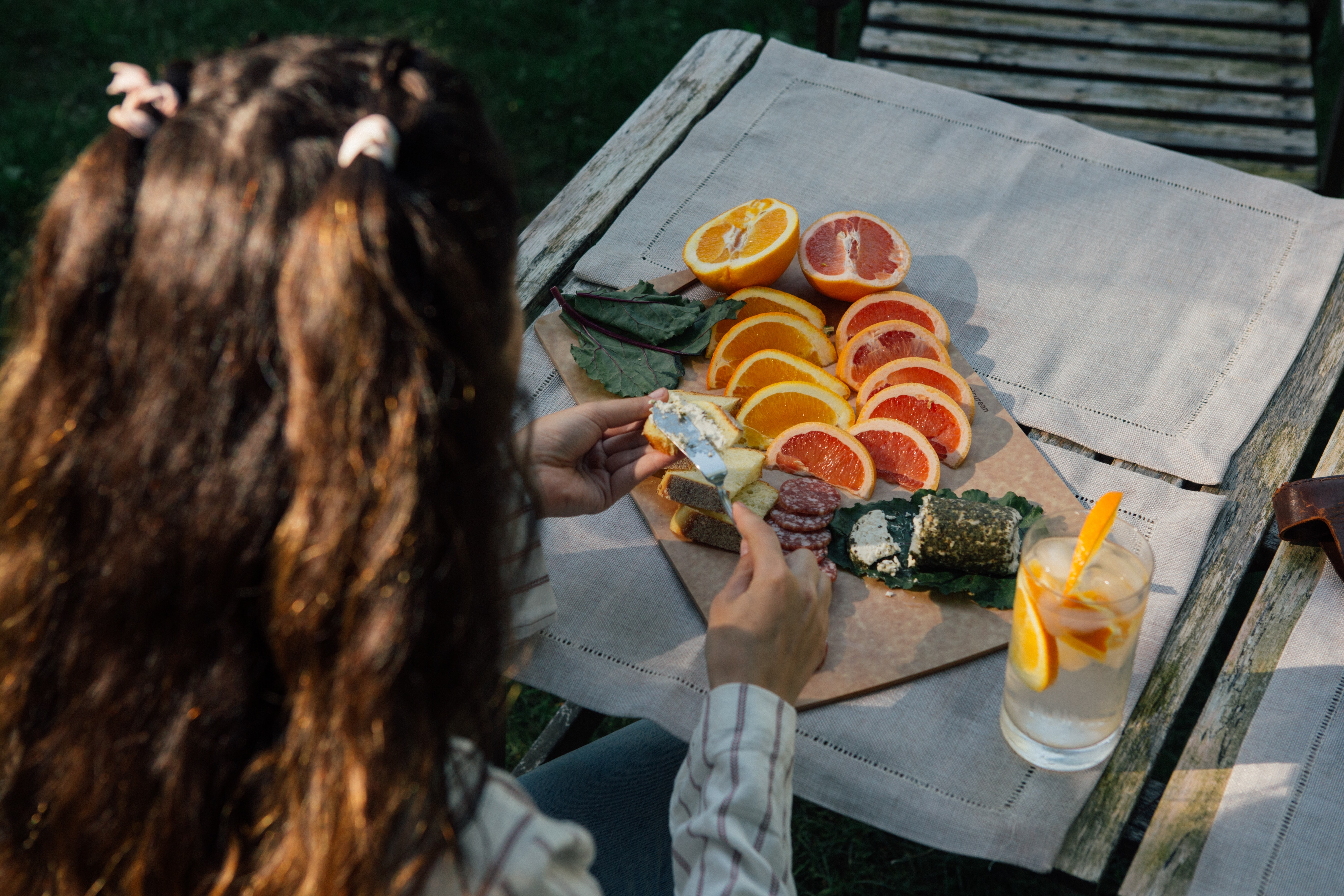 person holding slice fruits near gray wooden table close-up photo
