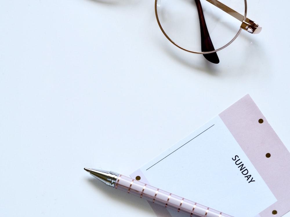 eyeglasses near paper and ballpoint pen