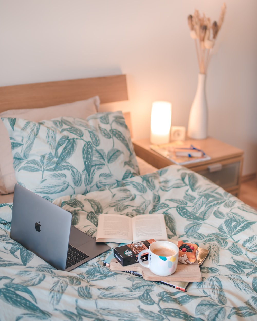 silver MacBook on top of white-and-blue bedding set
