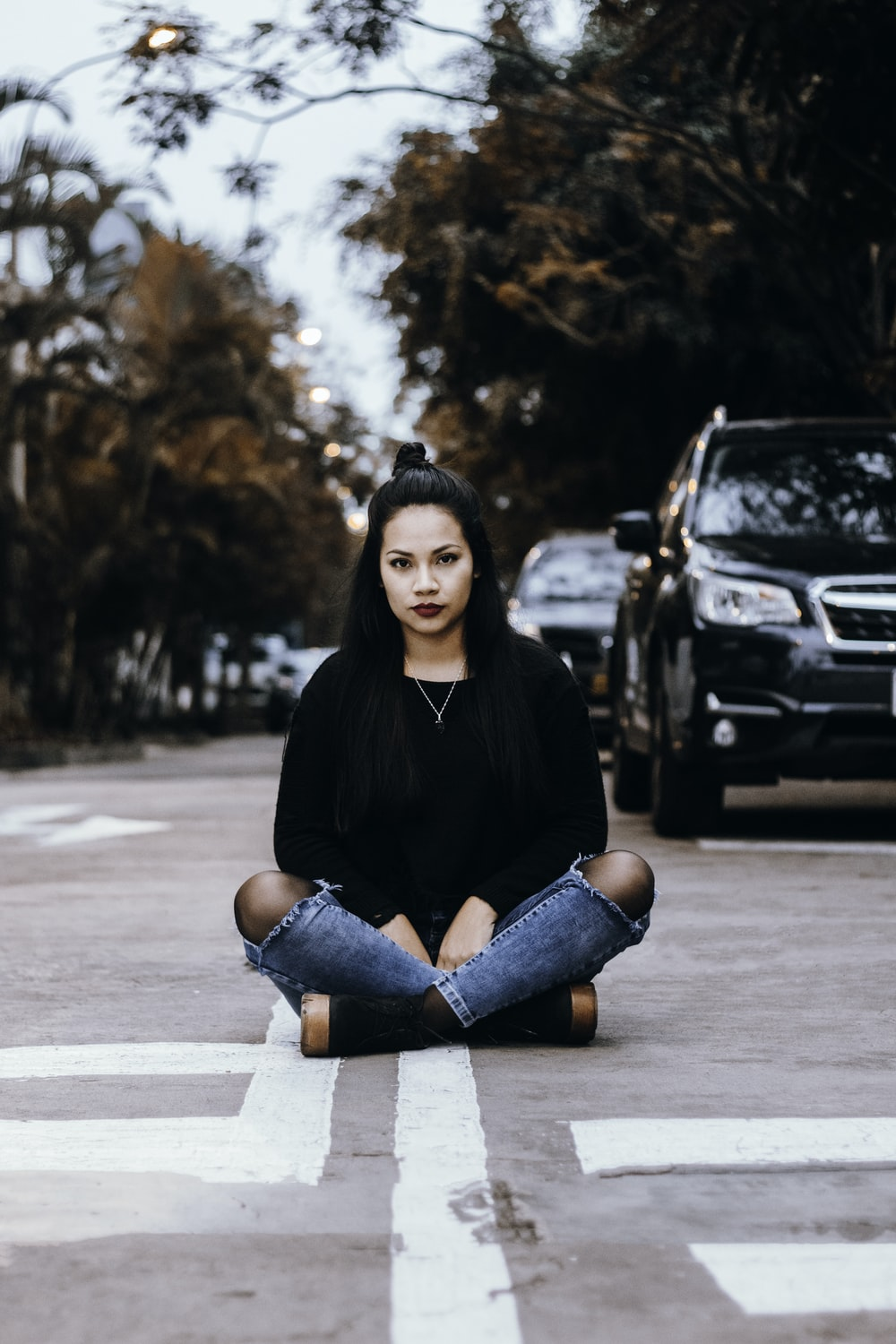 focus photography of woman sitting on gray concrete road during daytime