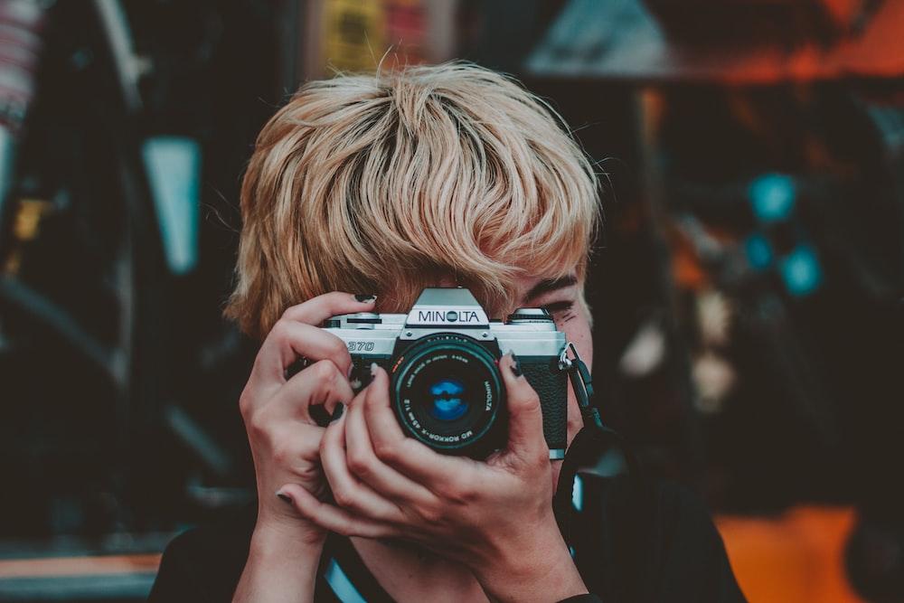 person holding gray and black Minolta SLR camera