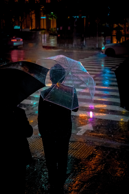 man wearing black suit jacket holding clear umbrella in front of pedestrian lane