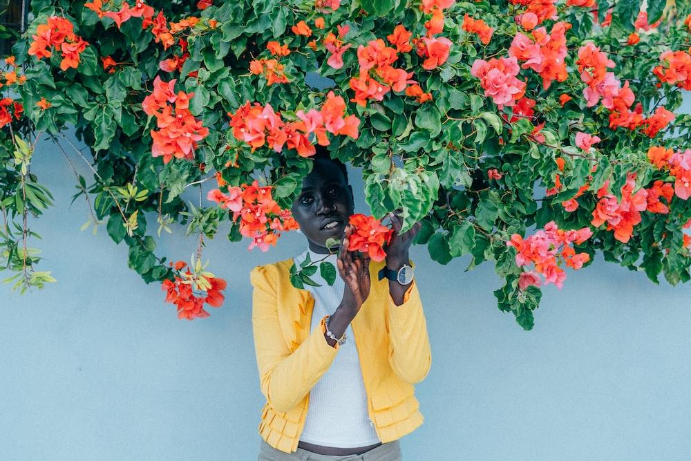 woman standing under orange petaled flower with green leaf plant