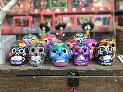 multi-colored sugar skull figurines mariachi teams background