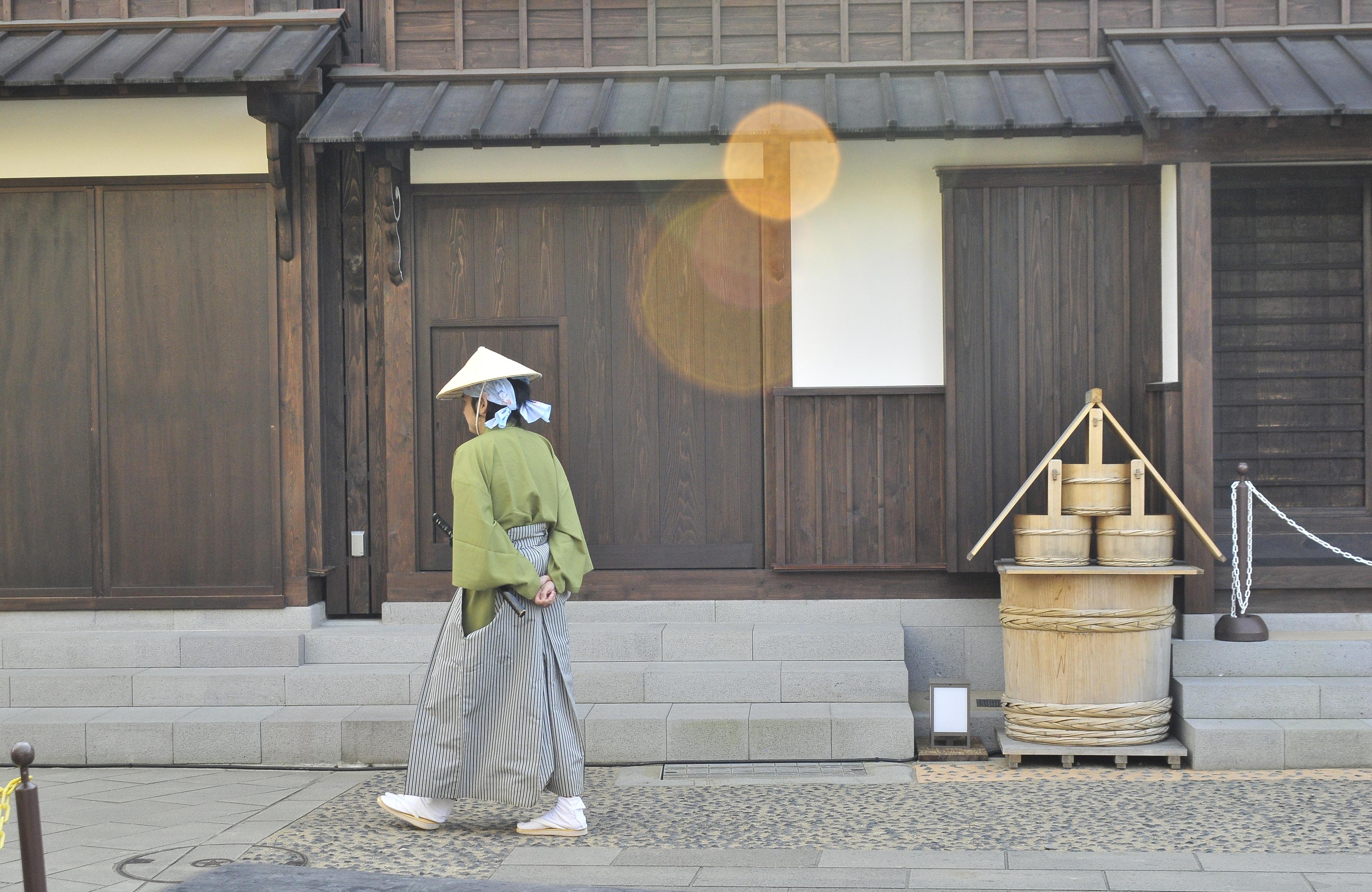 woman walking beside house