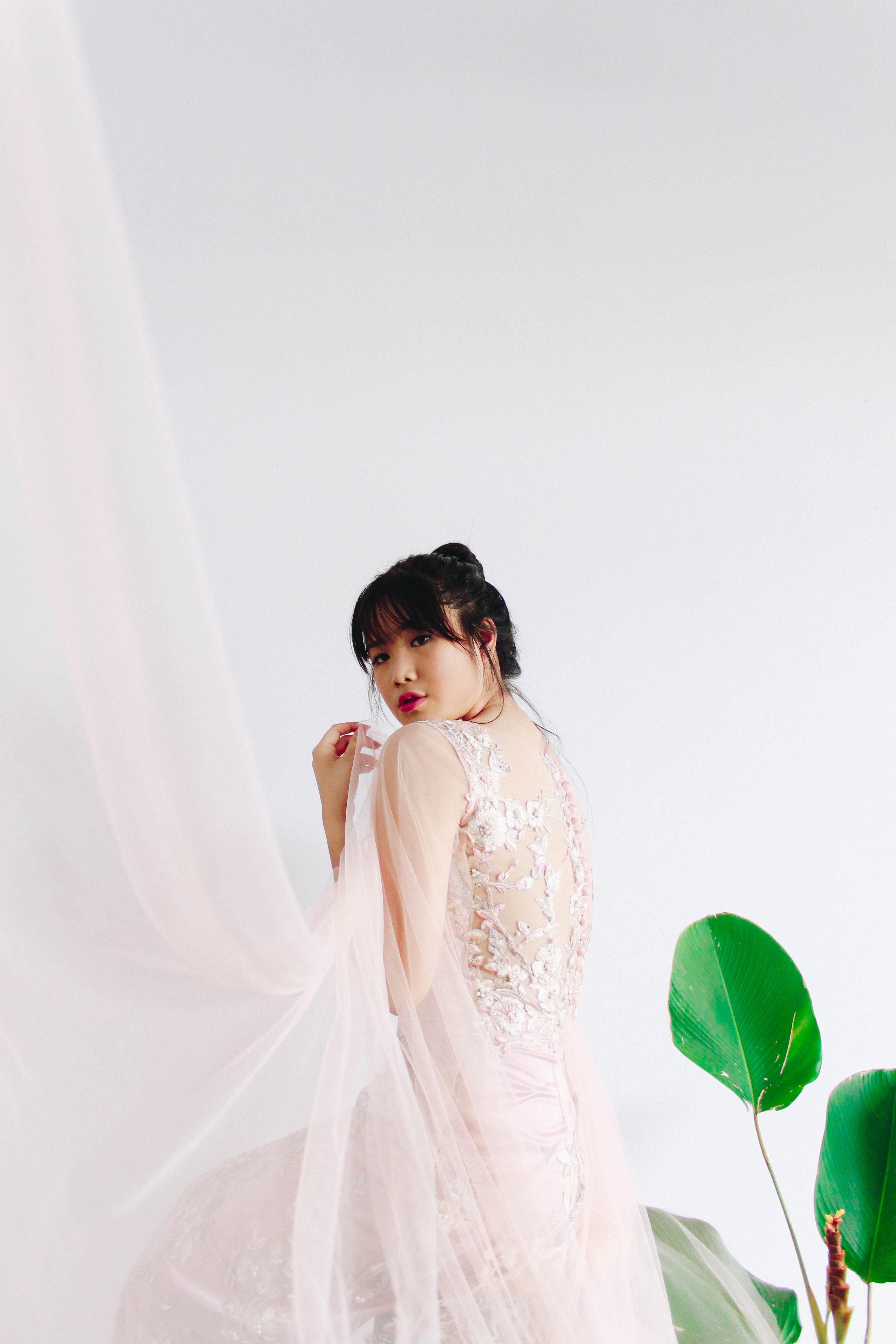 woman wearing white floral sleeveless wedding dress