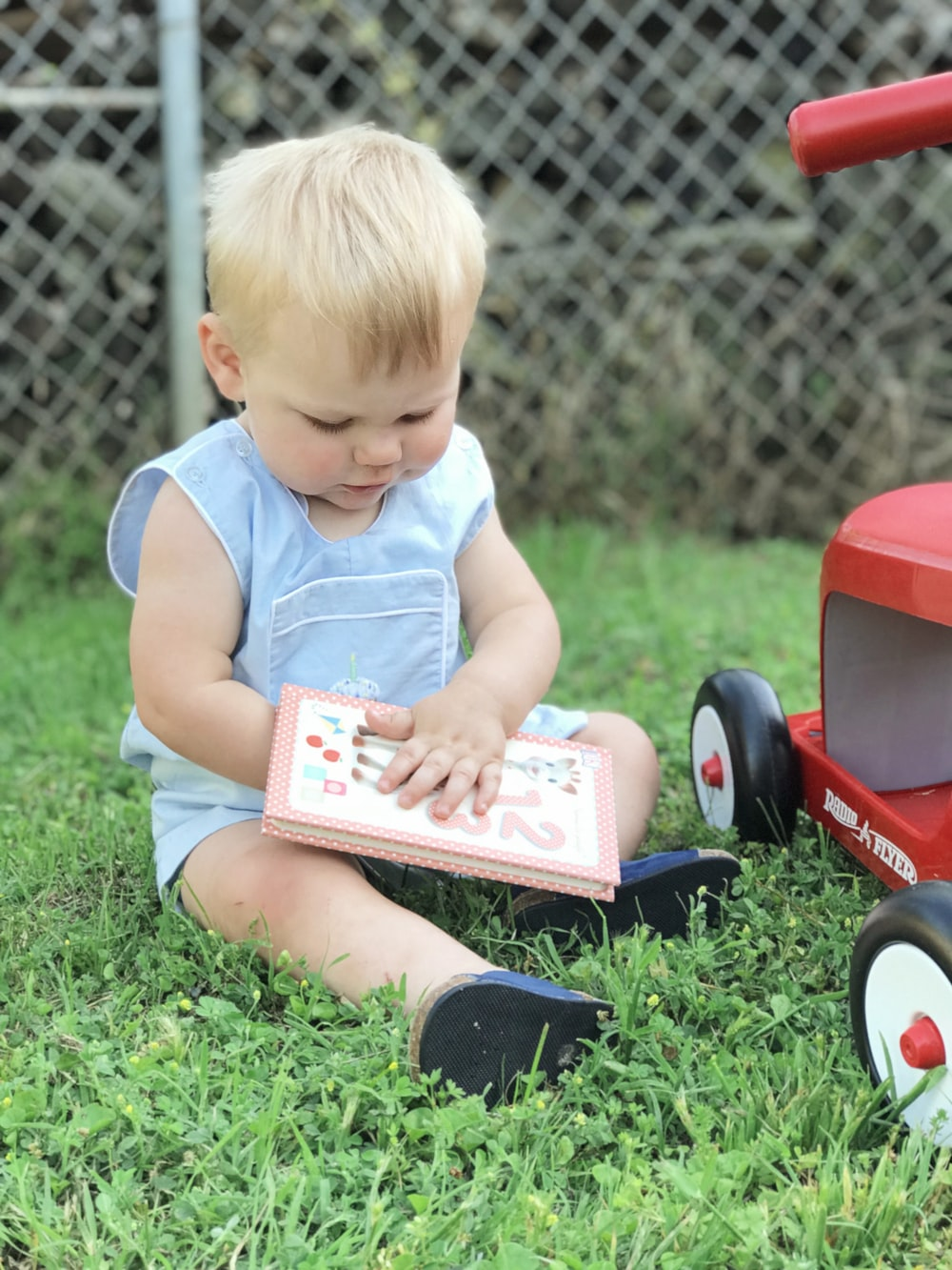 toddler sitting on grass during day