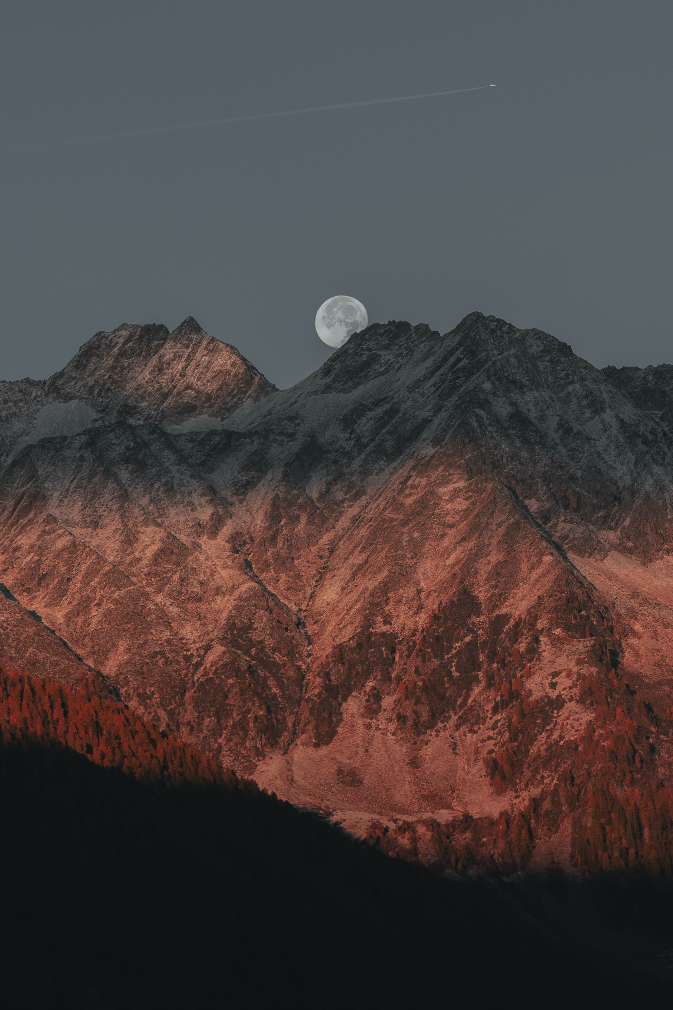 full moon hiding on mountain