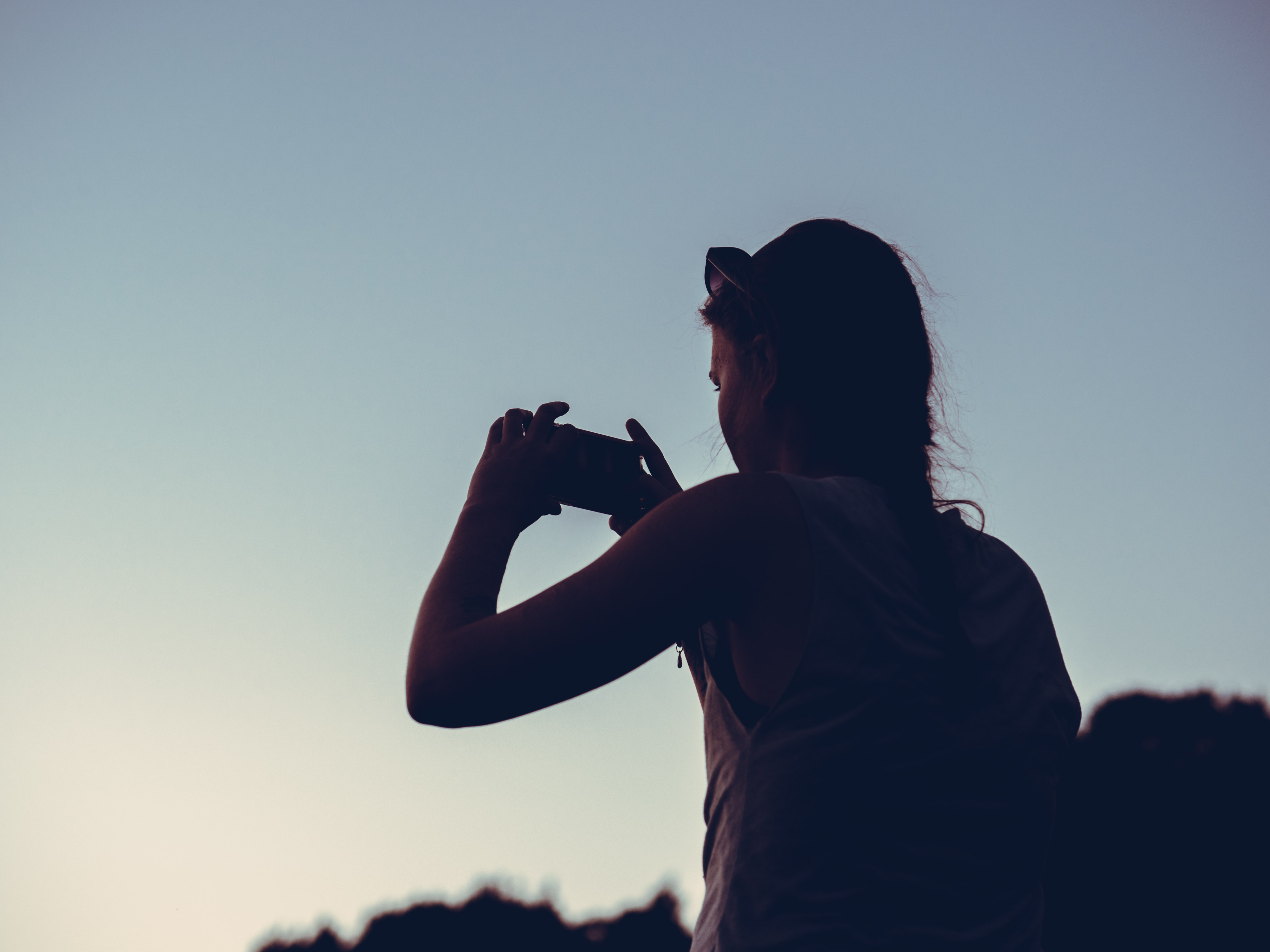 silhouette of woman taking photo of sunrise