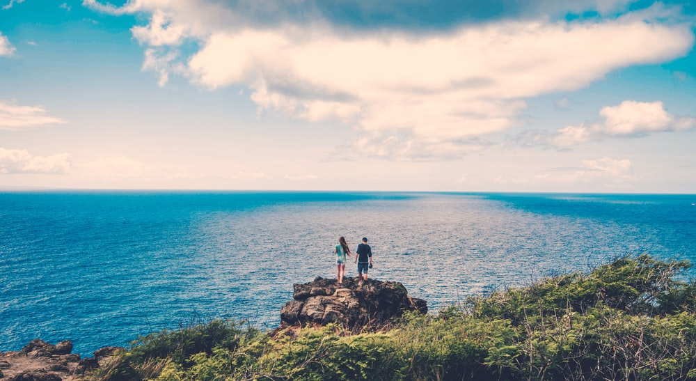 two persons on cliff near body of water
