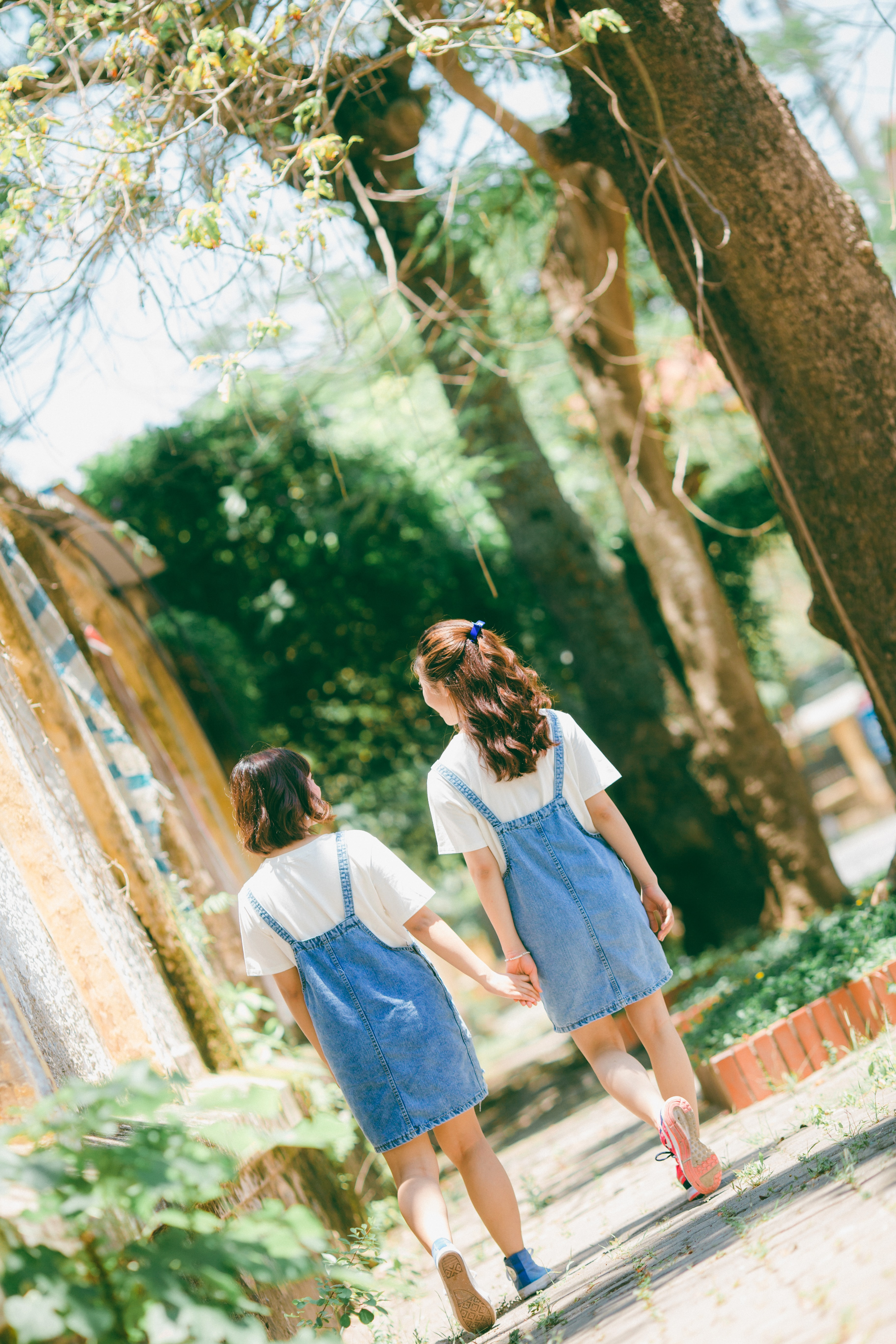 two women walking while holdings hands besides trees