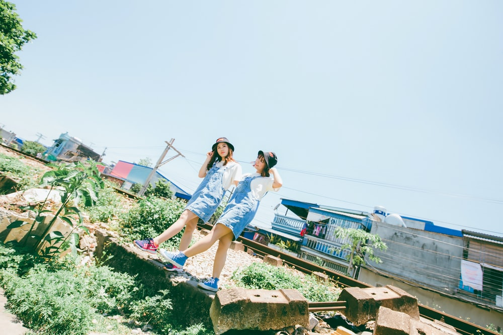 two girls walking on grass area