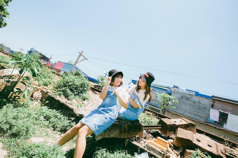 two women sitting on debris during daytime