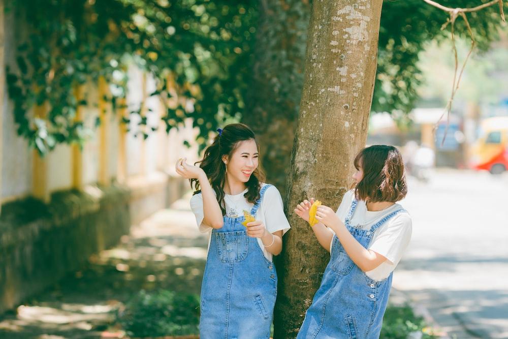two women wearing blue denim tops