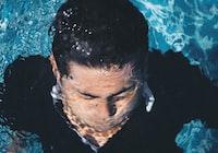 man in blue top underwater during daytime
