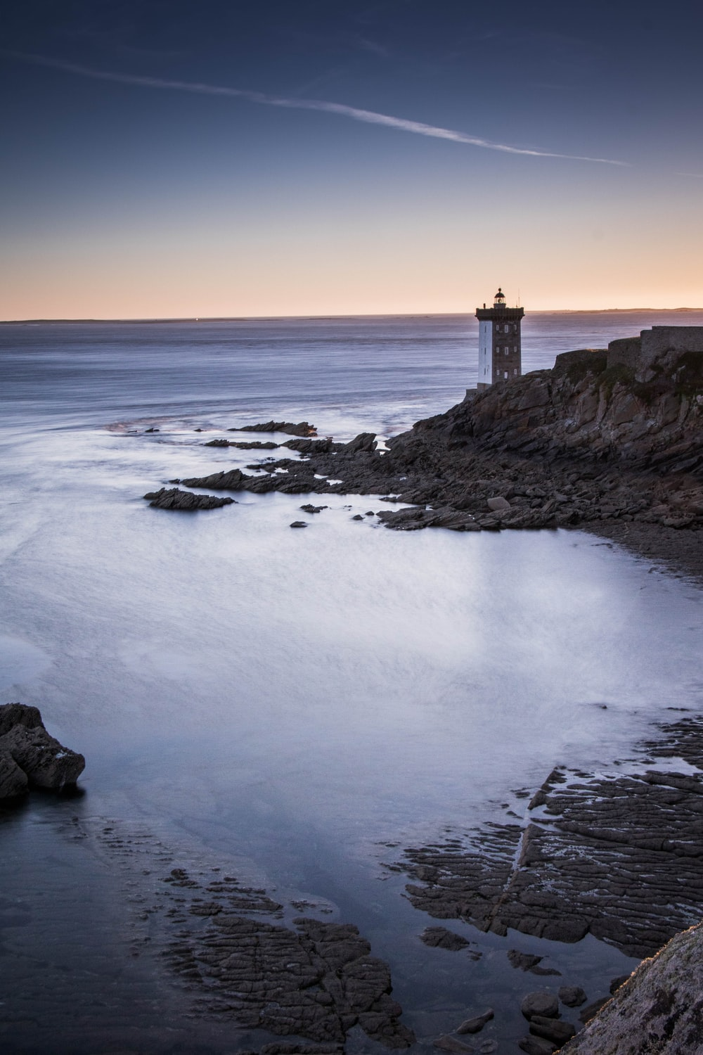 lighthouse near body of water during low tide