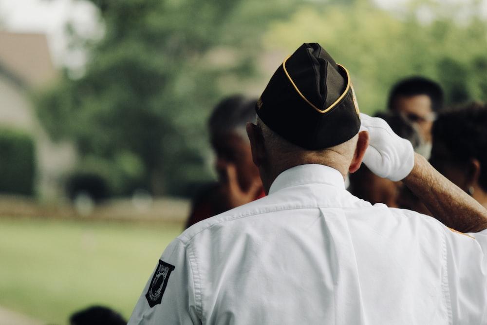 man wearing white uniform saluting