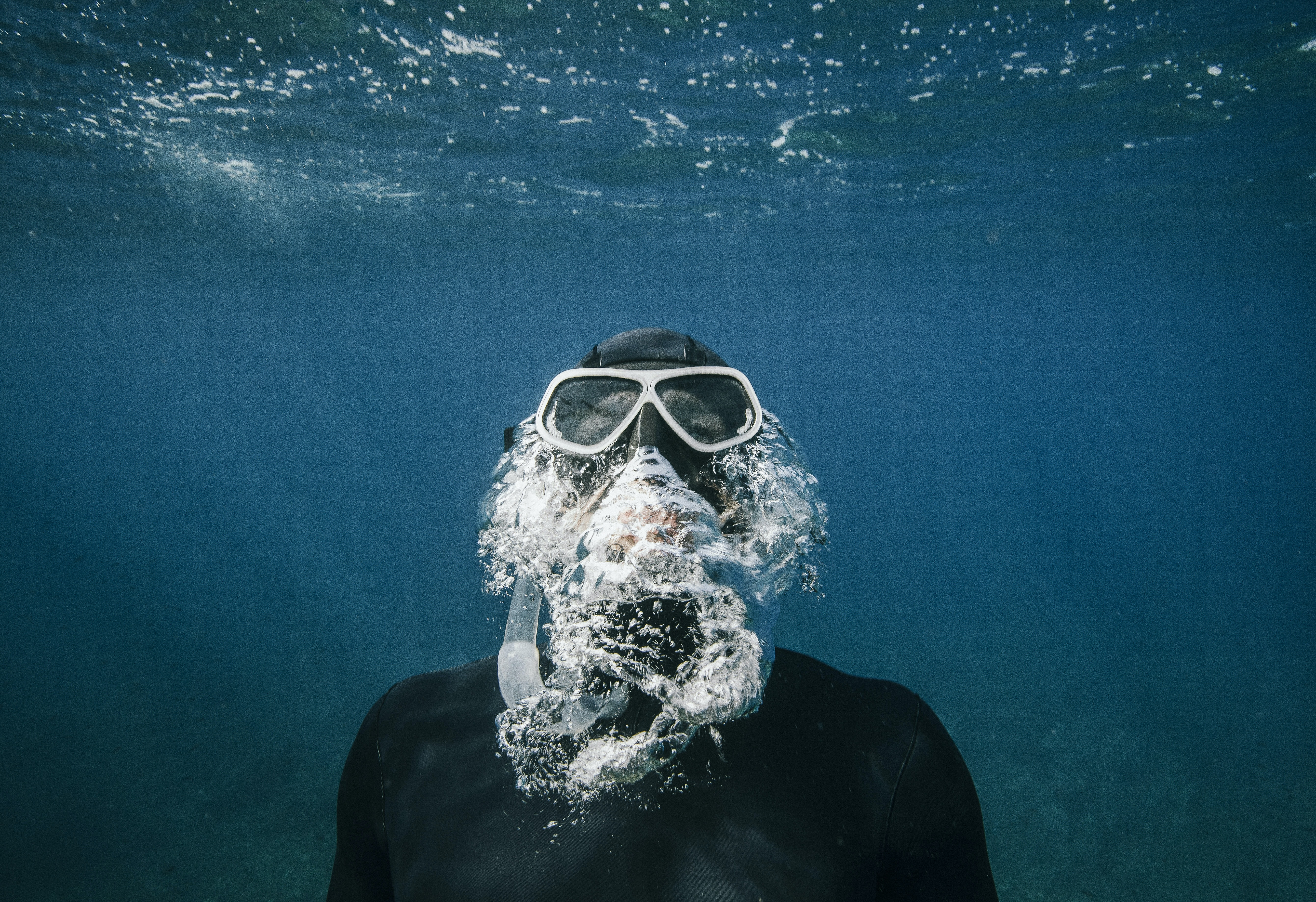 person with snorkle and goggles swimming underwater